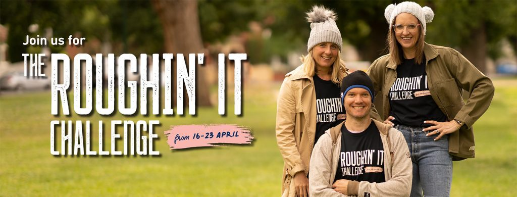 Three people stand in Roughin It Challenge t-shirts with jackets and woolly hats.